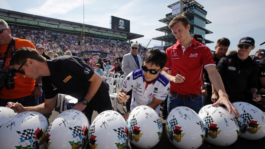 Ryan Hunter-Reay, left, Takuma Sato, of Japan, center, and Jack Hawksworth, of England, signs helmets before the drivers meeting for the Indianapolis 500 auto race at Indianapolis Motor Speedway in Indianapolis, Saturday, May 23, 2015.  (AP Photo/Darron Cummings)