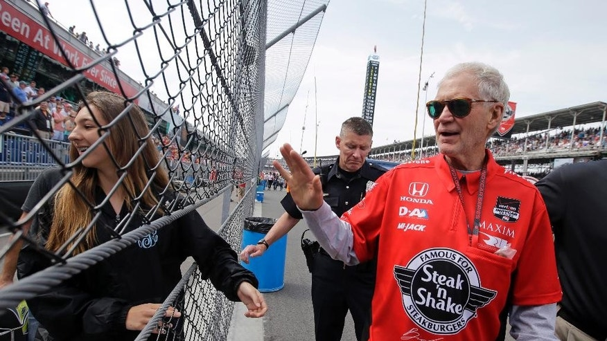 David Letterman, who ended his 33-year career as a late-night television host Wednesday, waves to fans as he walks through the pit area before the 99th running of the Indianapolis 500 auto race at Indianapolis Motor Speedway in Indianapolis, Sunday, May 24, 2015.  (AP Photo/Darron Cummings)
