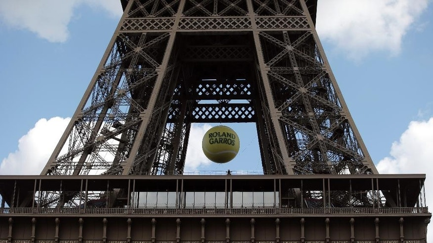 A giant tennis ball is hung under the second floor of the Eiffel Tower in Paris, Saturday, May 23, 2015 a day prior to the start of the French Tennis Open,  at the Roland Garros Stadium. (AP Photo/Francois Mori)
