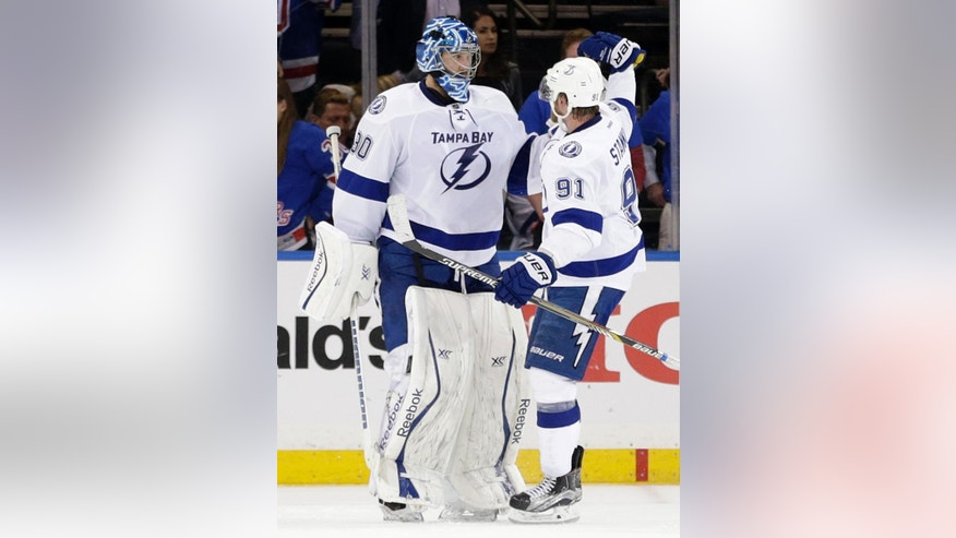 Tampa Bay Lightning center Steven Stamkos (91) congratulates Tampa Bay Lightning goalie Ben Bishop (30) after Bishop shut out the New York Rangers 2-0 in Game 5 of the Eastern Conference final during the NHL hockey Stanley Cup playoffs, Sunday, May 24, 2015, in New York. (AP Photo/Frank Franklin)