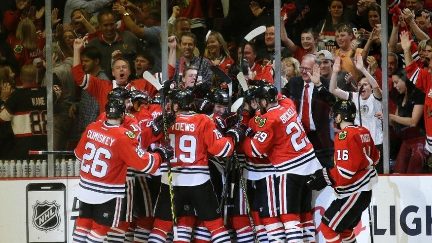 Chicago Blackhawks players celebrate Antoine Vermette's goal against the Anaheim Ducks during the second overtime in Game 4 of the Western Conference finals of the NHL hockey Stanley Cup Playoffs, Saturday, May 23, 2015, in Chicago. The Blackhawks won 5-4. (AP Photo/Nam Y. Huh)