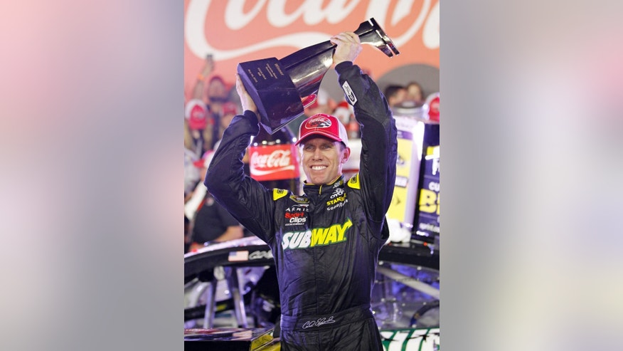 Carl Edwards raises the trophy in Victory Lane after winning the NASCAR Sprint Cup series auto race at Charlotte Motor Speedway in Concord, N.C., Sunday, May 24, 2015. (AP Photo/Terry Renna)