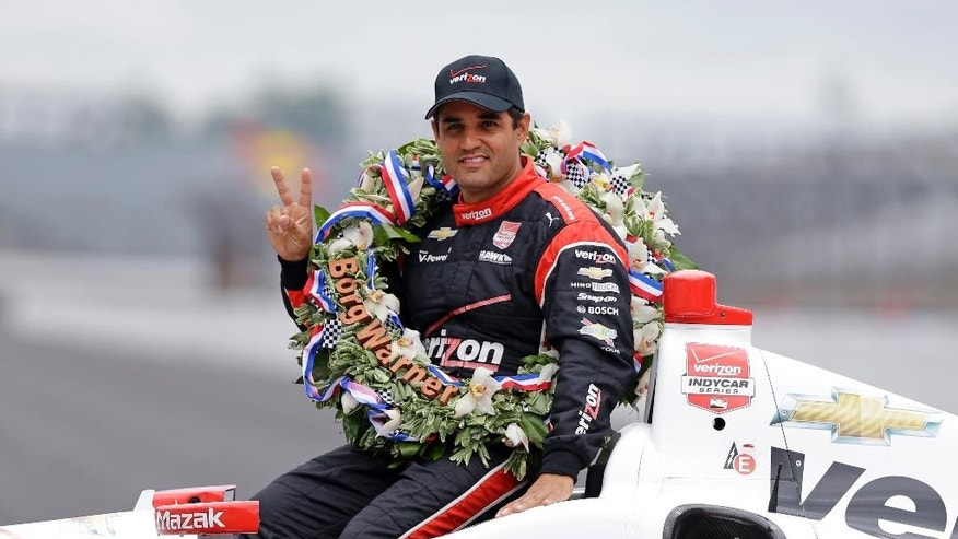 Juan Pablo Montoya, of Colombia, poses in his car during the traditional winners photo session at Indianapolis Motor Speedway in Indianapolis, Monday, May 25, 2015. Montoya won the 99th running of the Indianapolis 500 auto race on Sunday.  (AP Photo/Michael Conroy)