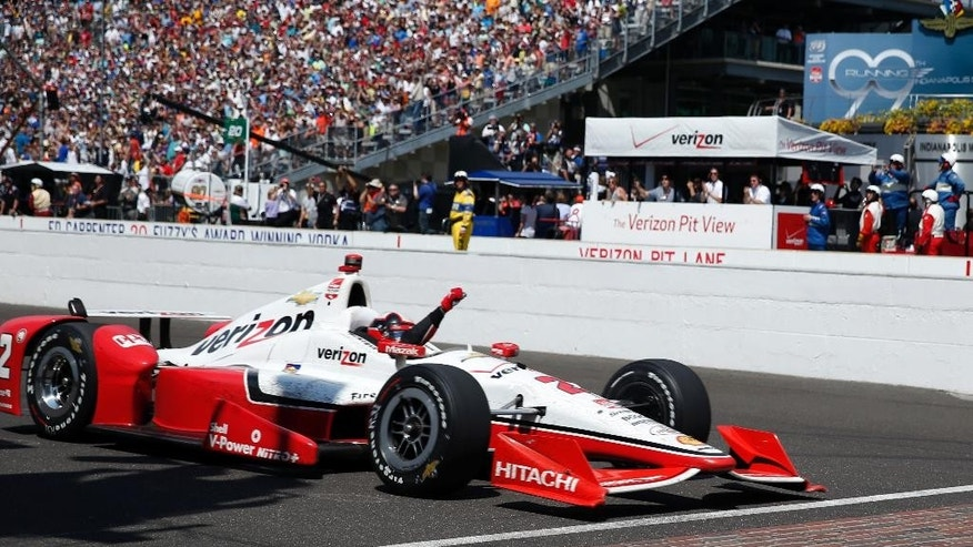 Juan Pablo Montoya, of Colombia,  celebrates as he crosses the finish line to win the 99th running of the Indianapolis 500 auto race at Indianapolis Motor Speedway in Indianapolis, Sunday, May 24, 2015.  (AP Photo/Rob Baker)