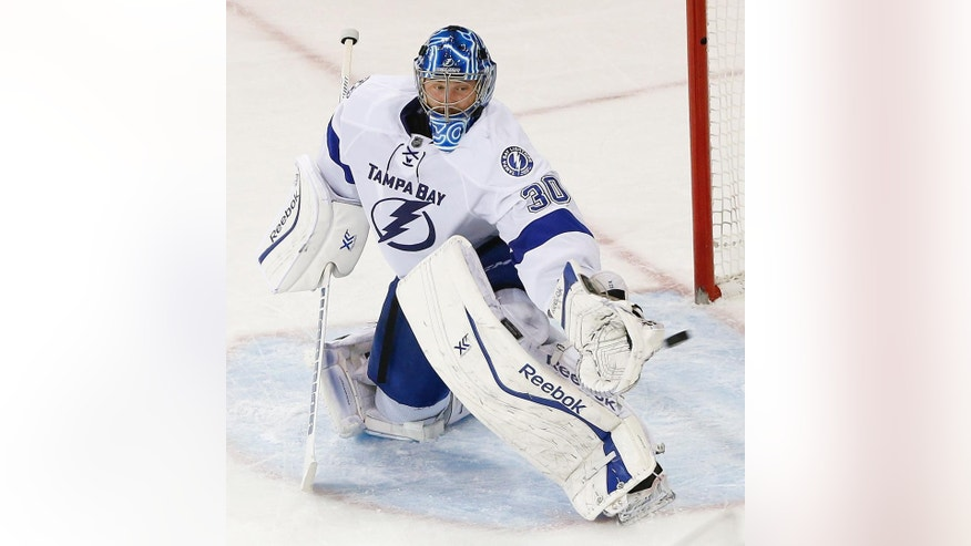 Tampa Bay Lightning goalie Ben Bishop (30) deflects a shot by the New York Rangers during the third period of Game 5 of the Eastern Conference final during the NHL hockey Stanley Cup playoffs, Sunday, May 24, 2015, in New York. The Lightning won 2-0. (AP Photo/Kathy Willens)