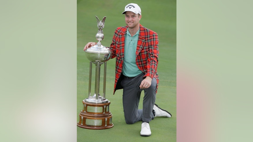 Chris Kirk poses with the champion's trophy after winning the Colonial golf tournament, Sunday, May 24, 2015, in Fort Worth, Texas. (AP Photo/LM Otero)
