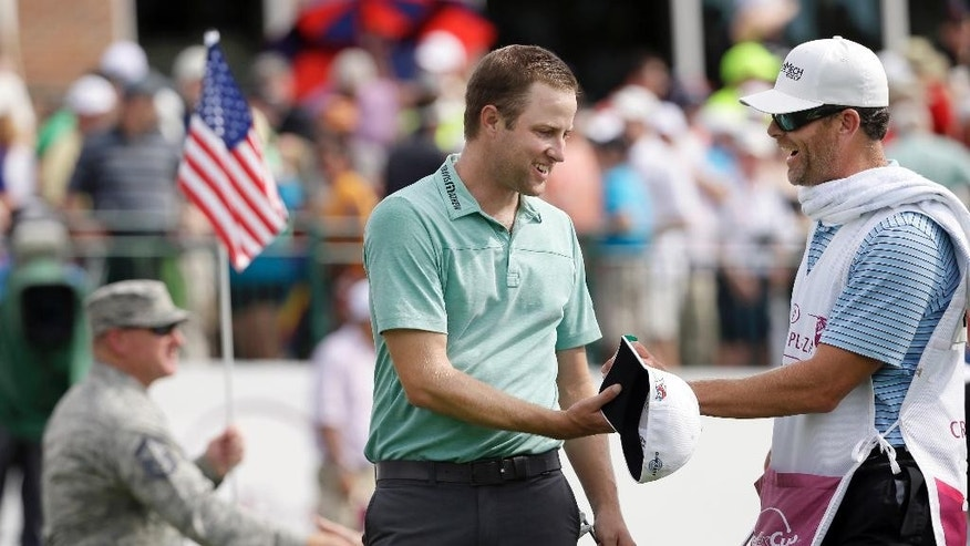 Chris Kirk, front left, shakes hands with his caddie G.W. Cable after finishing the Colonial golf tournament, Sunday, May 24, 2015, in Fort Worth, Texas.  Kirk won the tournamen. (AP Photo/LM Otero)