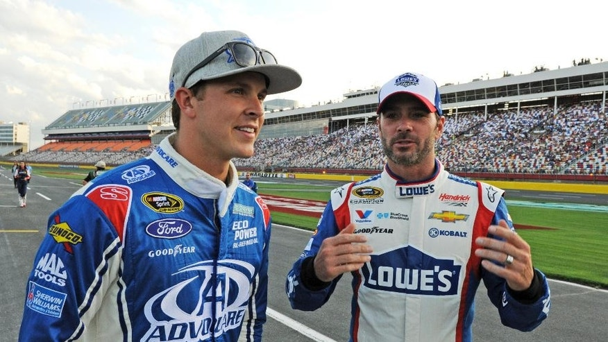 Jimmie Johnson, right, talks with Trevor Bayne before qualifying for Sunday's NASCAR Sprint Cup series auto race at Charlotte Motor Speedway in Concord, N.C., Thursday, May 21, 2015. (AP Photo/Mike McCarn)