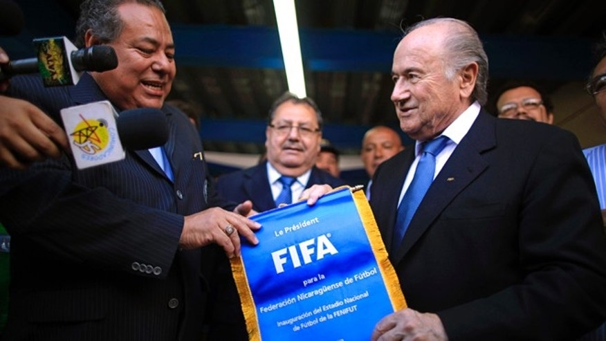 FILE - In this Thursday April 14, 2011 file photo FIFA President Sepp Blatter, right, gives a FIFA pennant to Nicaragua's Soccer Federation President Julio Rocha during the inauguration of the construction of a new National Soccer Stadium in Managua, Nicaragua. Rocha is among the soccer officials that were arrested and detained by Swiss police on Wednesday, May 27, 2015, at the request of U.S. authorities after a raid at Baur au Lac Hotel in Zurich. (AP Photo/Esteban Felix, File)