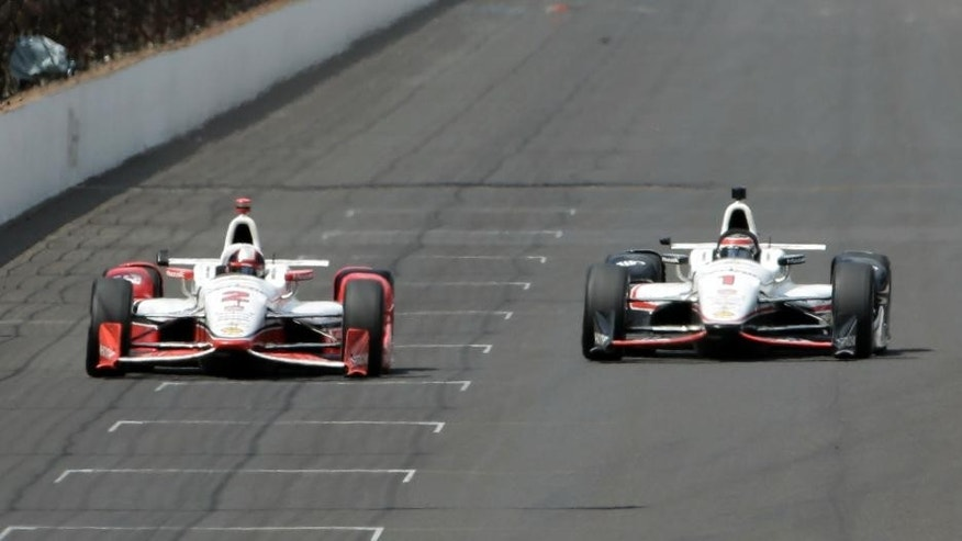 Juan Pablo Montoya, of Colombia, left, passes Will Power, of Australia, on lap198  on his way to winning during the 99th running of the Indianapolis 500 auto race at Indianapolis Motor Speedway in Indianapolis, Sunday, May 24, 2015.  (AP Photo/AJ Mast)