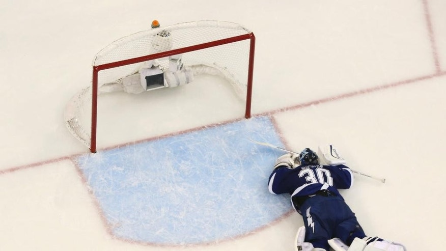 Tampa Bay Lightning goalie Ben Bishop (30) lies on the ice after allowing a goal during the third period of Game 6 of the Eastern Conference finals in the NHL hockey Stanley Cup playoffs, Tuesday, May 26, 2015, in Tampa, Fla. The Rangers defeated the Lightning 7-3. (AP Photo/Chris O'Meara)