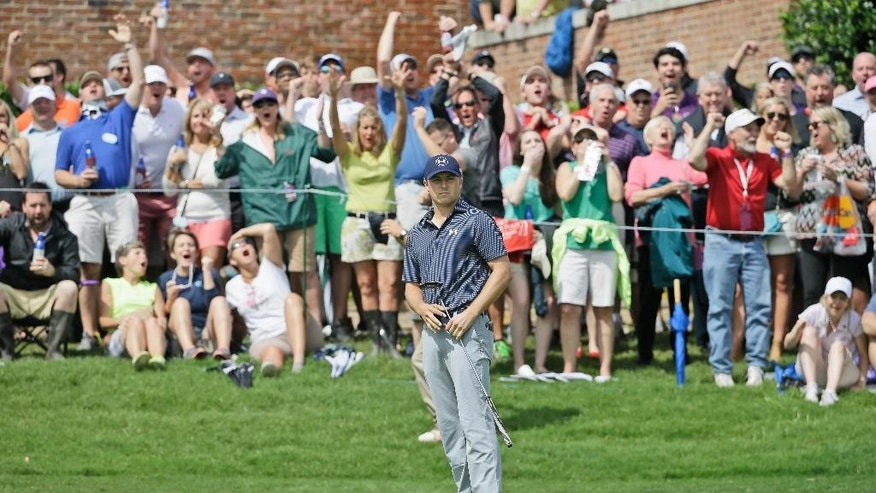 Jordan Spieth and the gallery watch his putt just miss the 16th hole during the final round of the Colonial golf tournament, Sunday, May 24, 2015, in Fort Worth, Texas. (AP Photo/LM Otero)