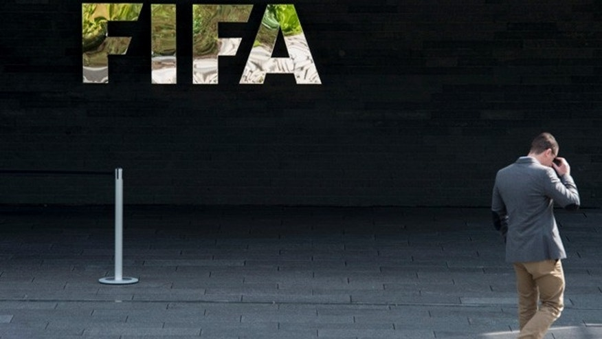 May 27, 2015: A man walks next to the FIFA logo at the FIFA headquarters in Zurich, Switzerland. Swiss federal prosecutors say they have opened criminal proceedings related to the awarding of the 2018 and 2022 World Cups. (Ennio Leanza/Keystone via AP)