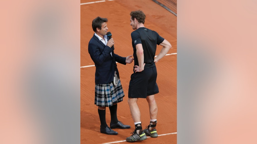 Former tennis player Fabrice Santoro of France sports a kilt as he interviews Britain's Andy Murray who won his second round match of the French Open tennis tournament against Portugal's Joao Sousa in four sets 6-2, 4-6, 6-4, 6-1, at the Roland Garros stadium, in Paris, France, Thursday, May 28, 2015. (AP Photo/Christophe Ena)