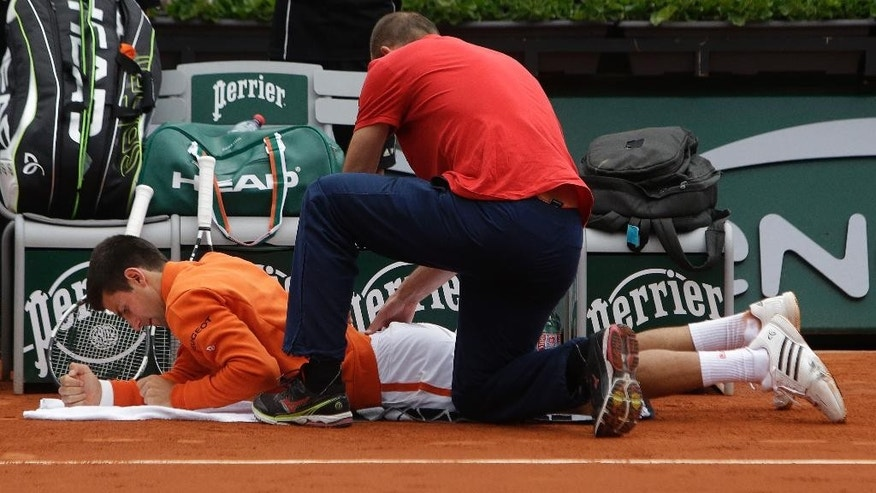 Serbia's Novak Djokovic is treated for an injury in the second round match of the French Open tennis tournament against Luxembourg's Gilles Muller at the Roland Garros stadium, in Paris, France, Thursday, May 28, 2015. (AP Photo/Thibault Camus)