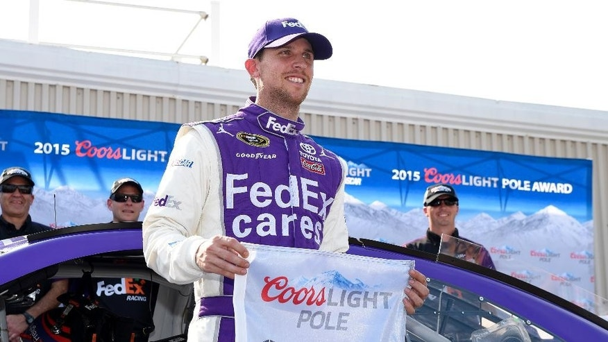 Denny Hamlin poses with the pole award after he won the position for Sunday's NASCAR Sprint Cup series auto race, Friday, May 29, 2015, at Dover International Speedway in Dover, Del. (AP Photo/Nick Wass)