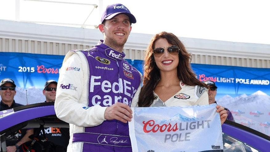 Denny Hamlin, left, poses with the pole award after he won the pole during qualifying for Sunday's NASCAR Sprint Cup series auto race, Friday, May 29, 2015, at Dover International Speedway in Dover, Del. (AP Photo/Nick Wass)