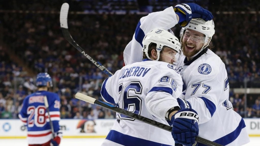 Tampa Bay Lightning right wing Nikita Kucherov (86) and Tampa Bay Lightning defenseman Victor Hedman (77) celebrate a third period goal by left wing Ondrej Palat (18) against the New York Rangers during Game 7 of the Eastern Conference final during the NHL hockey Stanley Cup playoffs, Friday, May 29, 2015, in New York.  (AP Photo/Frank Franklin)