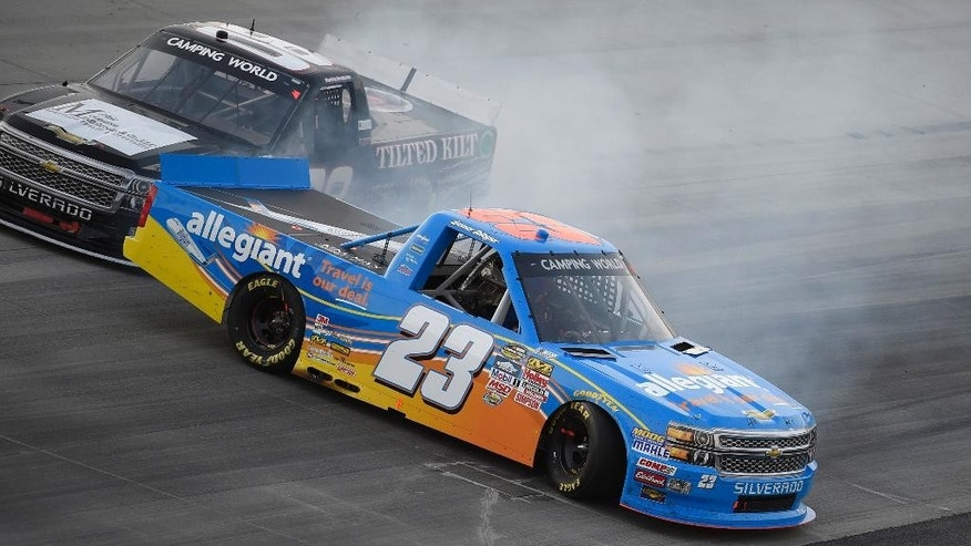 Spencer Gallagher (23) gets sideways next to Korbin Forrister, top, during a NASCAR Trucks series auto race, Friday, May 29, 2015, at Dover International Speedway in Dover, Del. (AP Photo/Nick Wass)