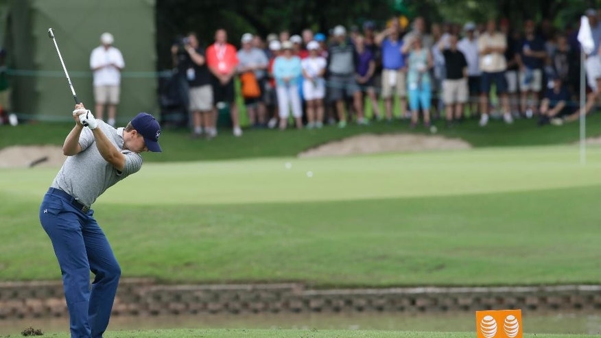 Jordan Spieth hits a tee shot on the shortened 14th hole during the second round of the Byron Nelson golf tournament, Friday, May 29, 2015, in Irving, Texas. The 14th fairway was washed over by a flash flood so the the hole was shortened to a 100-yard par 3. (AP Photo/LM Otero)