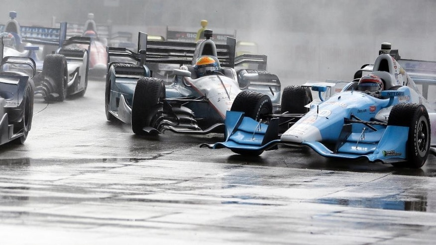 James Jakes of England, center, slides into Tony Kanaan of Brazil on the first turn during the first race of the IndyCar Detroit Grand Prix auto racing doubleheader Saturday, May 30, 2015, in Detroit. Colombian Carlos Munoz won the rain shortened race. (AP Photo/Carlos Osorio)
