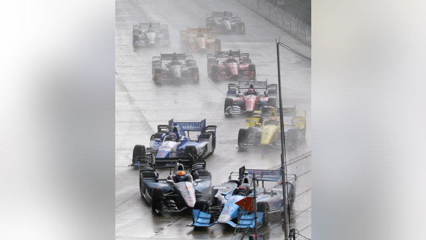 James Jakes of England, bottom left, slides into Tony Kanaan of Brazil on the first turn during the first race of the IndyCar Detroit Grand Prix auto racing doubleheader Saturday, May 30, 2015, in Detroit. (AP Photo/Dave Frechette)