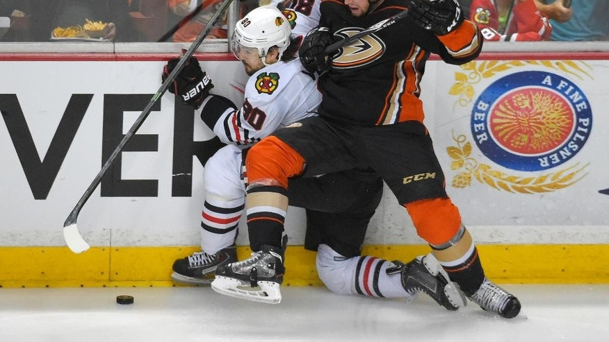 Anaheim Ducks left wing Matt Beleskey, right, checks Chicago Blackhawks center Antoine Vermette during the first period in Game 7 of the Western Conference final of the NHL hockey Stanley Cup playoffs in Anaheim, Calif., Saturday, May 30, 2015.  (AP Photo/Mark J. Terrill)