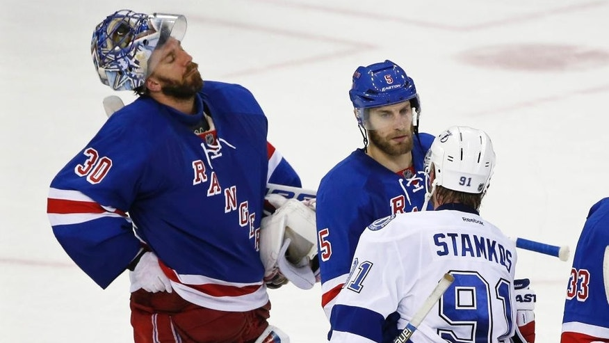 New York Rangers goalie Henrik Lundqvist (30) reacts as defenseman Dan Girardi (5) congratulates Tampa Bay Lightning center Steven Stamkos (91) after the Lightning beat the Rangers 2-0 in Game 7 of the Eastern Conference final during the NHL hockey Stanley Cup playoffs, Friday, May 29, 2015, in New York. (AP Photo/Kathy Willens)