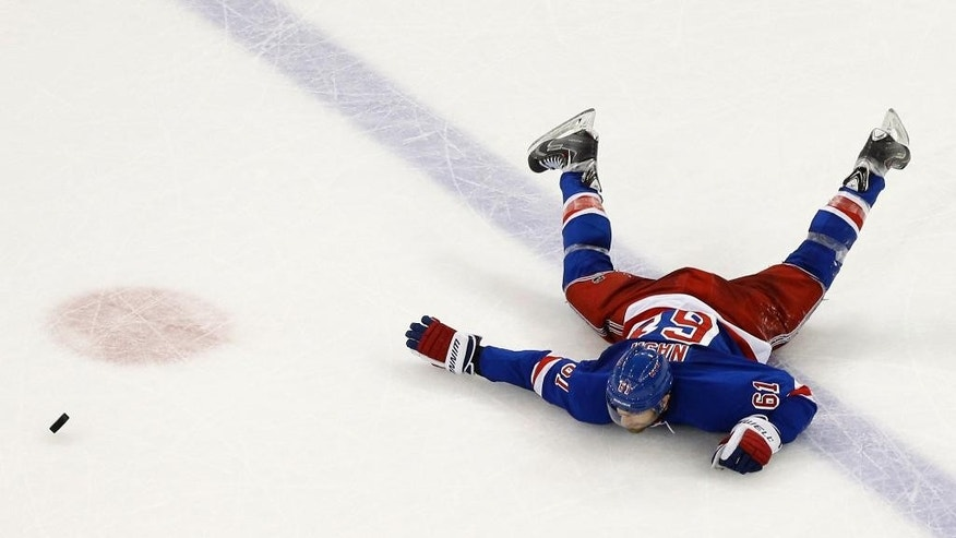 New York Rangers left wing Rick Nash hits the ice after losing his stick during the second period of Game 7 of the Eastern Conference final against the Tampa Bay Lightning during the NHL hockey Stanley Cup playoffs, Friday, May 29, 2015, in New York.  (AP Photo/Julie Jacobson)