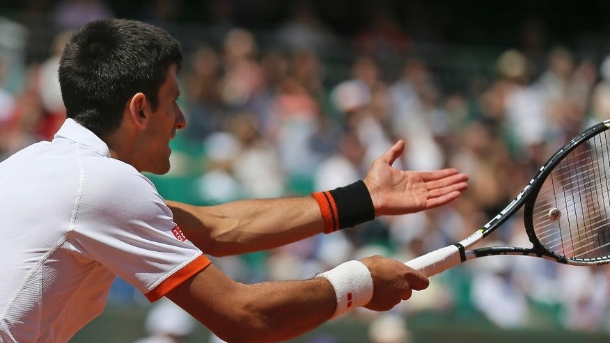 Serbia's Novak Djokovic gestures after missing a return in the third round match of the French Open tennis tournament against Thanissi Kokkakis of Australia at the Roland Garros stadium, in Paris, France, Saturday, May 30, 2015. (AP Photo/David Vincent)