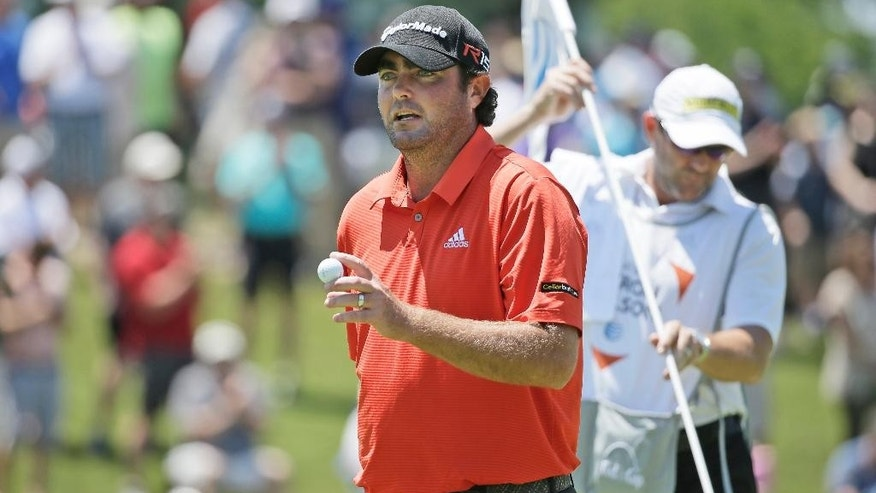Steven Bowditch acknowledges the gallery after sinking a putt on the first hole during the final round of the Byron Nelson golf tournament, Sunday, May 31, 2015, in Irving, Texas. (AP Photo/LM Otero)