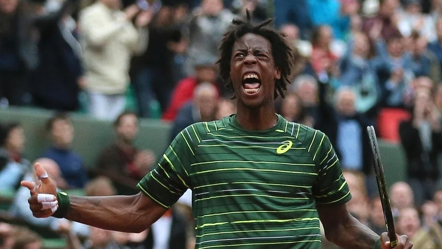 France's Gael Monfils screams after scoring a point in the fourth round match of the French Open tennis tournament against Switzerland's Roger Federer at the Roland Garros stadium, in Paris, France, Sunday, May 31, 2015. (AP Photo/David Vincent)