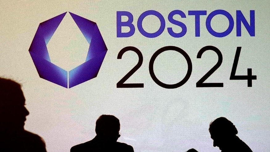FILE - In this Jan. 21, 2015 file photo, shadows of organizers and reporters pass a video display screen prior to a news conference by organizers of Boston's campaign for the 2024 Summer Olympics in Boston. Public hearings debating the pros and cons of the embattled bid have become increasingly bitter, and the gap between opponents and supporters appears to be widening. Meetings have featured profanity and shouting matches, and the issue is rife with online venom. (AP Photo/Charles Krupa, File)