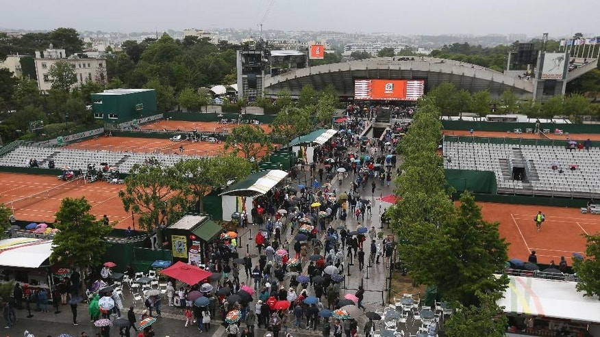 Spectators with umbrellas walk in the alleys after rain suspended matches of the French Open tennis tournament at the Roland Garros stadium, in Paris, France, Sunday, May 31, 2015. (AP Photo/David Vincent)