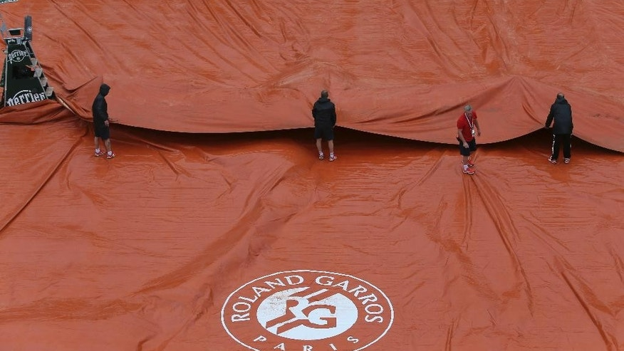 Stadium employees cover Philippe Chatrier court, known as center court, as rain suspended matches of the French Open tennis tournament at the Roland Garros stadium, in Paris, France, Sunday, May 31, 2015. (AP Photo/David Vincent)