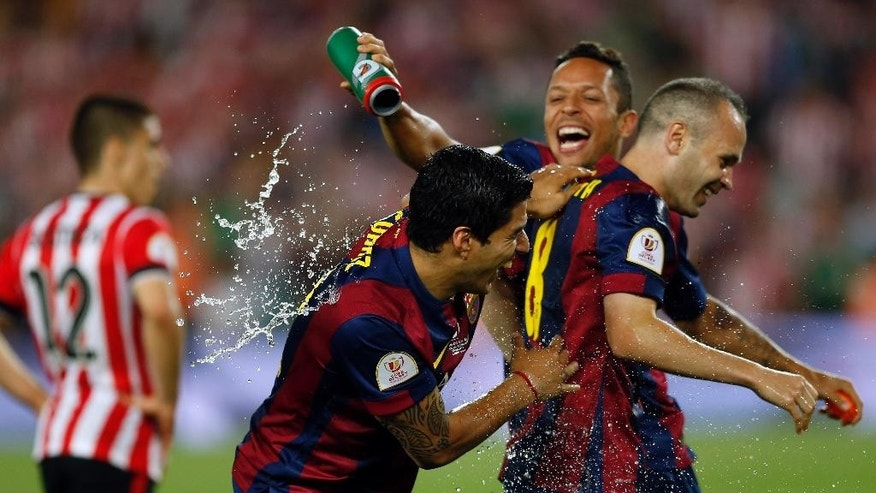 Barcelona's Luis Suarez, Adriano Correia and Andres Iniesta, from left to right, celebrate after winning the final of the Copa del Rey soccer match between FC Barcelona and Athletic Bilbao at the Camp Nou stadium in Barcelona, Spain, Saturday, May 30, 2015. (AP Photo/Manu Fernandez)