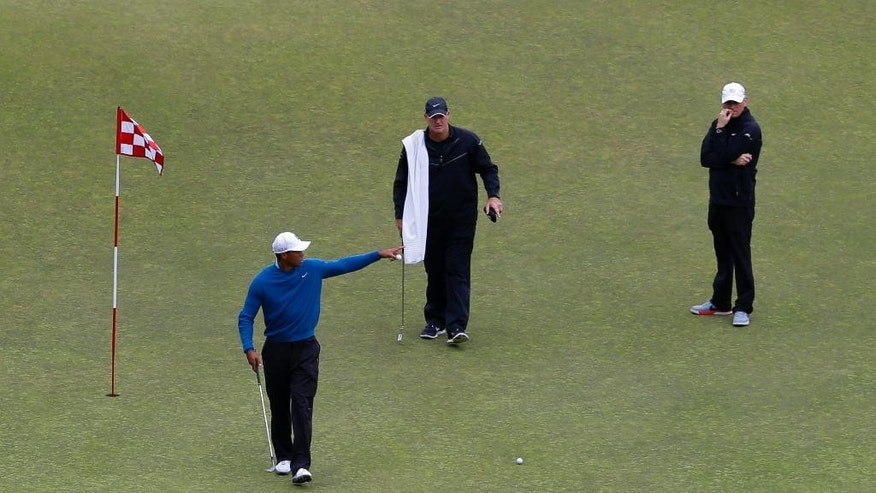 Tiger Woods, left, gestures as he practices on the ninth green, Tuesday, June 2, 2015, at Chambers Bay in University Place, Wash., where the U.S. Open golf tournament will be played June 18-21. (AP Photo/Ted S. Warren)