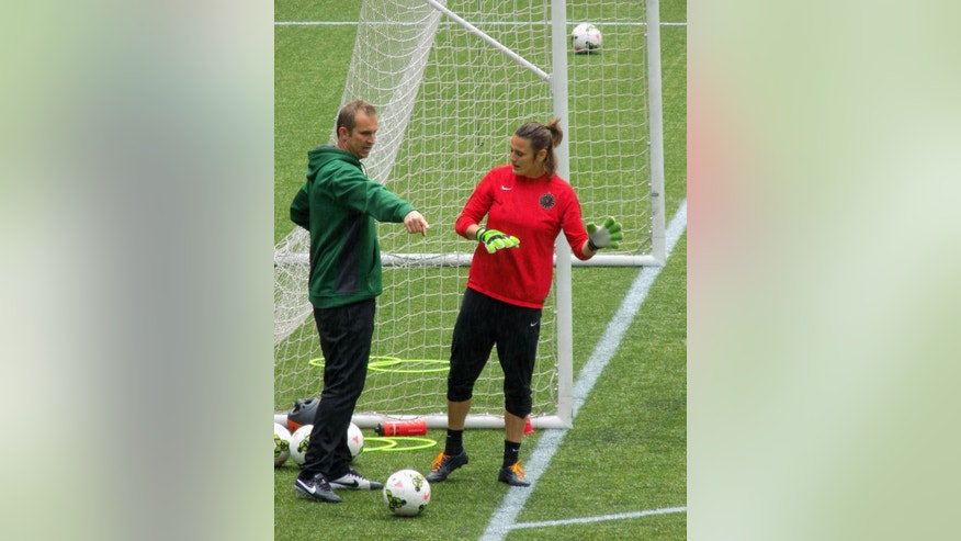 In this photo taken May 5, 2015, goalkeeper Nadine Angerer works out in the rain with Portland Thorns goalkeeper coach Scott Vallow in Portland, Ore. Angerer was playing briefly for her National Women's Soccer League team before rejoining the German national team in preparation for the Women's World Cup in Canada. (AP Photo/Anne M. Peterson)