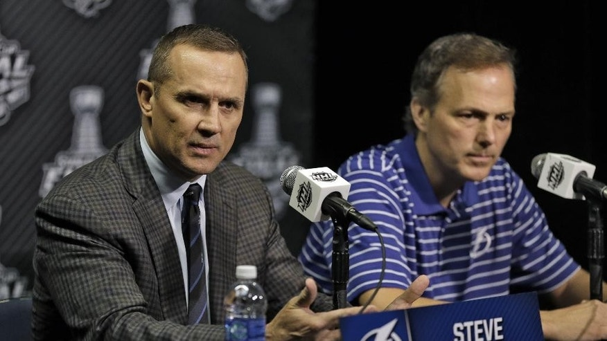 Tampa Bay Lightning general manager Steve Yzerman, left, and head coach Jon Cooper answer questions during media day for the NHL Hockey Stanley Cup Finals, Tuesday, June 2, 2015, in Tampa, Fla. The Lightning will take on the Chicago Blackhawks in Game 1 on Wednesday.  (AP Photo/Chris O'Meara)