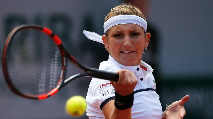 Timea Bacsinszky of Switzerland returns the ball to Belgium's Alison van Uytvanck Belgium's Alison van Uytvanck during their quarterfinal match of the French Open tennis tournament, at the Roland Garros stadium, Wednesday, June 3, 2015 in Paris. (AP Photo/Francois Mori)