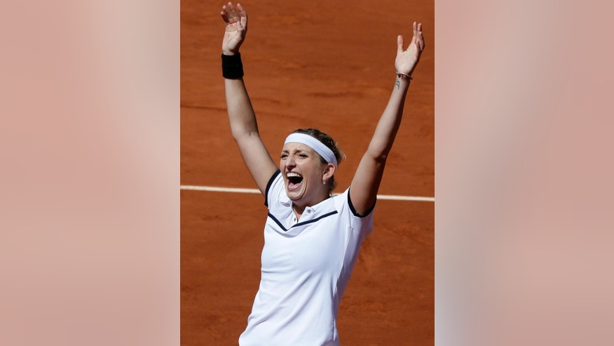 Timea Bacsinszky of Switzerland raises her arms as she defeats Belgium's Alison van Uytvanck during their quarterfinal match of the French Open tennis tournament, at the Roland Garros stadium, Wednesday, June 3, 2015 in Paris. Bacsinszky won 6-4, 7-5. (AP Photo/Thibault Camus)
