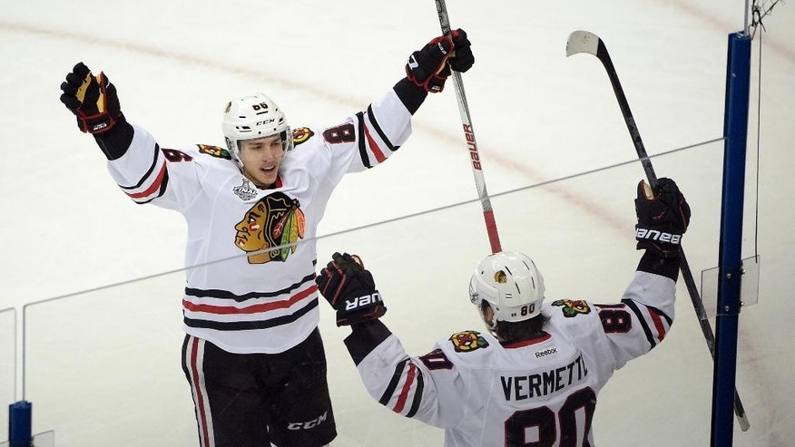 Chicago Blackhawks center Antoine Vermette (80) of Canada, celebrates his game winning goal with Teuvo Teravainen of Finland (86),  against the Tampa Bay Lightning during the third period in Game 1 of the NHL hockey Stanley Cup Final in Tampa, Fla., Wednesday, June 3, 2015.  The Blackhawks defeated the Lightning 2-1. (AP Photo/Phelan M. Ebenhack)