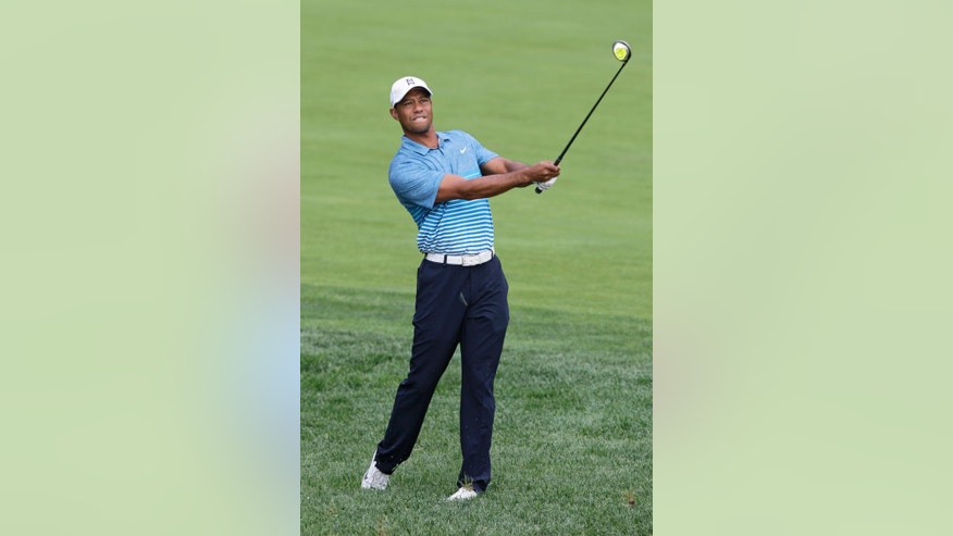 Tiger Woods watches his approach shot on the 18th hole during a practice round for The Memorial golf tournament, Wednesday, June 3, 2015, in Dublin, Ohio. (AP Photo/Jay LaPrete)
