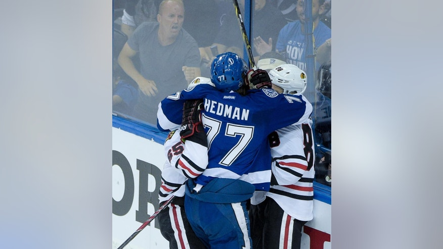 Tampa Bay Lightning defenseman Victor Hedman, middle, said he might have been bitten by Chicago Blackhawks center Andrew Shaw, left, while in a scrum with Patrick Kane during the first period in Game 1 of the NHL hockey Stanley Cup Final in Tampa, Fla., Wednesday, June 3, 2015.  (AP Photo/Phelan M. Ebenhack)