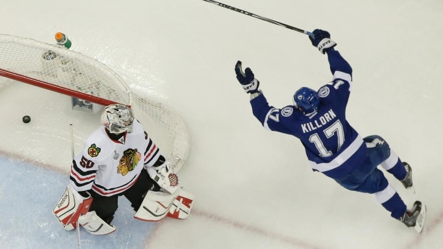 Chicago Blackhawks center Andrew Shaw (65) of Canada, left, shoots past Tampa Bay Lightning defenseman Braydon Coburn (55) of Canada,  during the third period in Game 1 of the NHL hockey Stanley Cup Final in Tampa, Fla., Wednesday, June 3, 2015. The Blackhawks defeated the Lightning 2-1.  (AP Photo/Phelan M. Ebenhack)