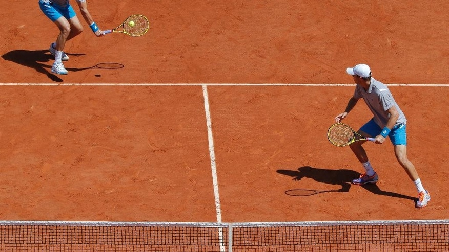 Bob, right, and Mike Bryan of the U.S. return in the men's double semifinal match of the French Open tennis tournament against Italy's Simone Bolelli and Fabio Fognini at the Roland Garros stadium, in Paris, France, Thursday, June 4, 2015. (AP Photo/Christophe Ena)