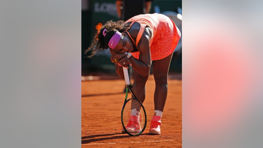 Serena Williams of the U.S. leans on her racket in her semifinal match of the French Open tennis tournament against Timea Bacsinszky of Switzerland at the Roland Garros stadium, in Paris, France, Thursday, June 4, 2015. (AP Photo/Francois Mori)