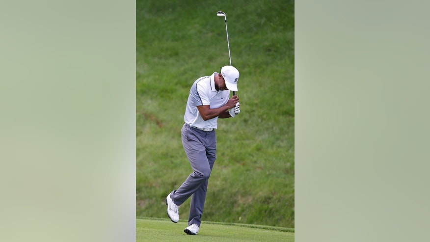 Tiger Woods reacts after hitting a shot on the 11th hole during the first round of the Memorial golf tournament Thursday, June 4, 2015, in Dublin, Ohio. (AP Photo/Darron Cummings)