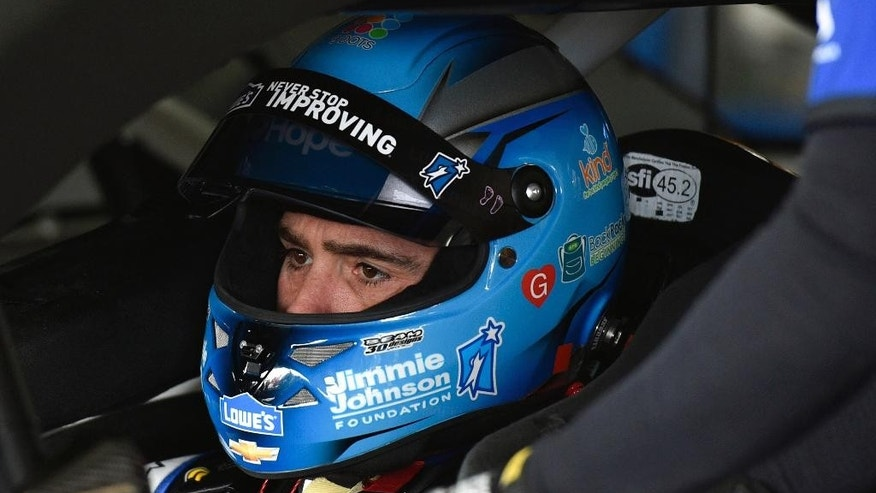 Jimmie Johnson waits in his car in the garage at Pocono Raceway during practice for Sunday's NASCAR Sprint Cup Series auto race in Long Pond, Pa., Friday, June 5, 2015. (AP Photo/Derik Hamilton)