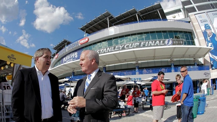 In this photo taken, Wednesday, June 3, 2015, Tampa Bay Lightning owner Jeff Vinik, left, chats with Tampa, Fla., Mayor Bob Buckhorn before Game 1 of the NHL hockey Stanley Cup Final in Tampa, Fla. While Sun Belt NHL teams from Phoenix to Miami struggle to maintain revenue and relevance in their communities, the Lightning are thriving. The franchise's second trip to the Stanley Cup Final is the highlight of a revival under owner Jeff Vinik as the organization builds a vibrant hockey town in a warm-weather climate. Game 2 is scheduled for Saturday night against the Chicago Blackhawks. (AP Photo/Chris O'Meara)